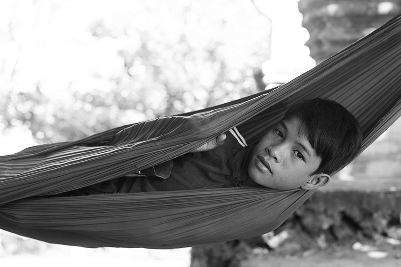 Portrait of a kid resting in a hammock in Battambang, Cambodia